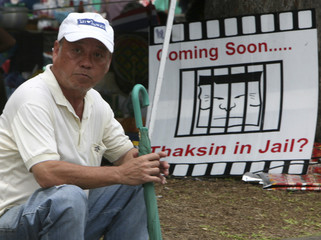 Member of PAD sits in front of banner during demonstration in Bangkok
