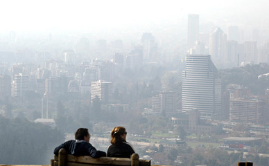 TOURISTS LOOK AT SANTIAGO SKYLINE COVERED BY SMOG.