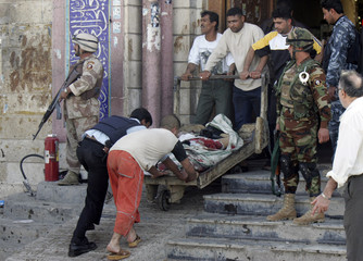 Rescuers remove a body from inside a mosque after a suicide bombing in central Baghdad