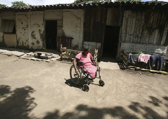 Montes, a landmine victim from Nicaragua's civil war in 1980s, wheels herself through San Francisco Libre town