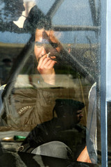 An Israeli border policeman is reflected a bus window at the check point on the entrance to Tul Karem.