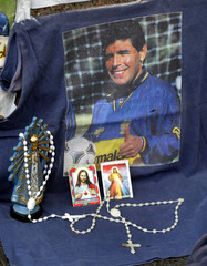 RELIGIOUS ICONS PLACED NEXT TO A PHOTO OF FORMER ARGENTINE SOCCER STAR MARADONA.