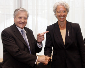 European Central Bank Chairman Trichet shakes hands with France's Finance Minister Lagarde ahead of meeting in Brussels
