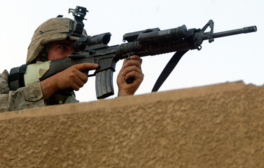 U.S. MARINES SOLDIER KEEPS WATCH FROM ROOF TOP NEARBY FALLUJA IRAQ.