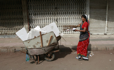 A female sweeper cleans the street outside of closed shops in Karachi