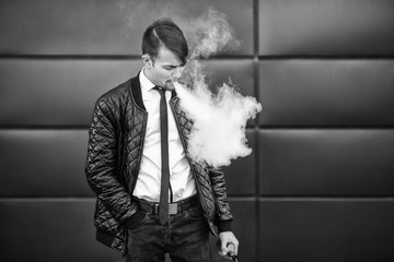 Vape man. Portrait of a handsome young white guy with modern haircut vaping and letting off steam from an electronic cigarette. Black and white photo. Lifestyle.