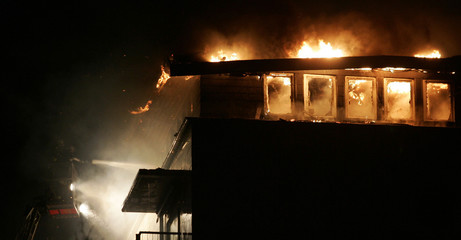 Firefighters on a ladder attempt to extinguish a fire in the roof truss of an apartment in city of Reinbek