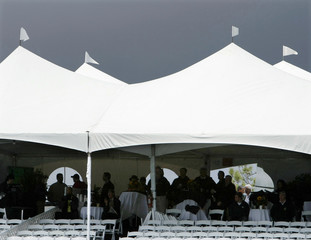 Golf fans gather under stormy skies as they watch from corporate box during Buick Invitation golf tournament in San Diego