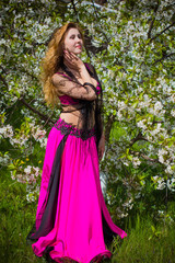 A beautiful girl from a harem in an oriental Arabic costume for belly dancing on the nature around lake walks and enjoys a sunny afternoon on the territory