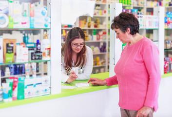 Female pharmacist discusses prescription medication with senior customer at pharmacy