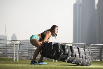 Strong Athletic Middle Eastern Girl lifts a large tire wearing sports bra and shorts with a cityscape in the background