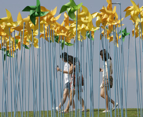 Women walk beside an art installation made up of weathercocks wishing for peace on the Korean peninsular, at Imjingak