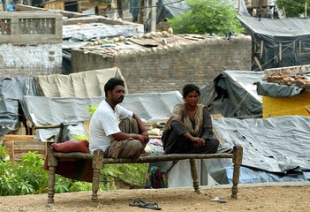 HINDU SLUM DWELLERS SIT ON A BED OUTSIDE THEIR HOUSE IN JAMMU.