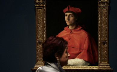 "A woman walks past the painting ""El cardenal"" by Italian artist Rafael in Madrid"