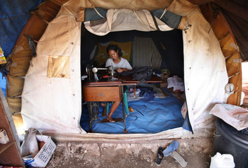 An East Timorese refugee mends a pair of pants inside her tent at Don Bosco Comoro camp