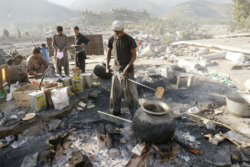 A Pakistani relief aid worker prepares food to be distributed among earthquake victims in Balakot