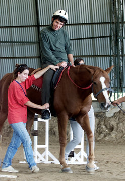 AUTISTIC MAN RIDES HORSE DURING THERAPY SESSION IN MONTEVIDEO.