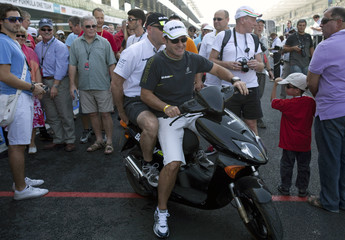 Brawn GP Formula One driver Barrichello of Brazil leaves the pit on a scooter ahead of the Abu Dhabi F1 Grand Prix at the Yas Marina circuit