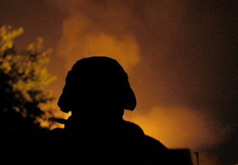A U.S. Marine, from the 24th Marine Expeditionary Unit, stands in front of house burned by Taliban fighters during heavy close range battle near the town of Garmser