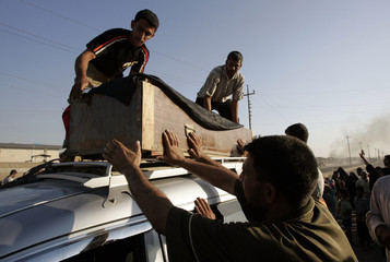 Men place a coffin on top of a vehicle during a funeral in Baghdad's Sadr City