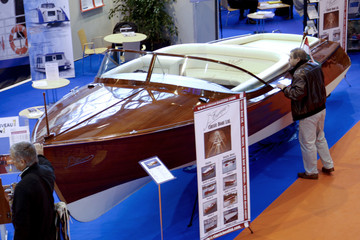 A visitor looks a wooden boat with an electric engine during the Paris Boat show