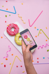 Party. Taking photo of different colourful sugary round glazed donuts