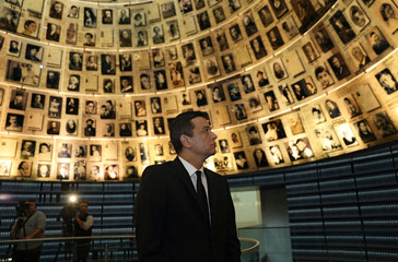 Sorin Grindeanu, Romania's Prime Minister, looks at pictures of Jews killed in the Holocaust during a visit to the Hall of Names at Yad Vashem's Holocaust History Museum in Jerusalem