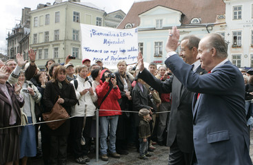Spain's King Juan Carlos and Estonia's President Toomas Hendrik Ilves wave to a crowd as they sightsee in Tallinn