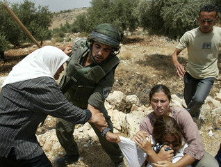 A Palestinian woman scuffles with an Israeli border policeman during a protest against the construct..