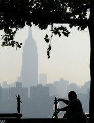 The haze shrouded skyline of New York is a backdrop to a man filling up water bottles along the Hudson River in Hoboken