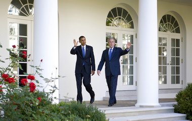 U.S. President George W. Bush and U.S. President-elect Barack Obama wave as they walk through the Collande at the White House in Washington.