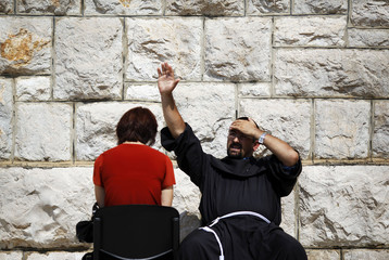 A Catholic priest raises his hand during confession near the site where the Virgin Mary reportedly appeared in an apparition in Medjugorje