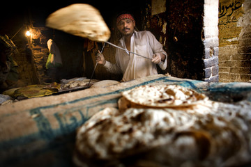 Baker takes a bread out of the oven in a kitchen in Lahore