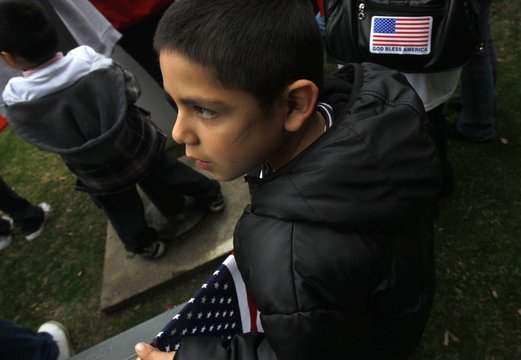 A boy takes part in a march to the Dallas US Citizenship and Immigration Services office to protest delays in the processing of their applications