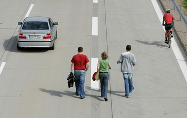 People walk on the A6 highway before the official opening of the last part between Nuremberg and Prague near Schmidgaden