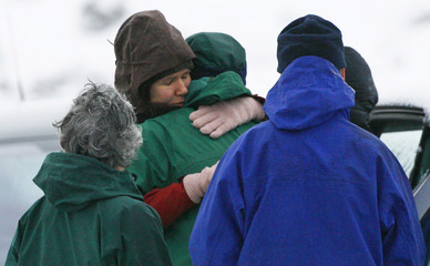 Surviving members of climbing party embrace after returning to their vehicles at base of Buachaille Etive Mor in Glencoe