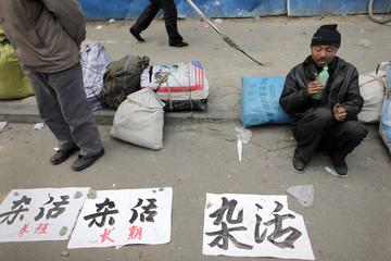Jobseeker smokes water pipe as he waits next to paper sheets describing his skills at a makeshift job market in Zhengzhou