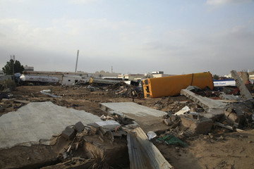 Damaged vehicles and houses are seen in Jeddah