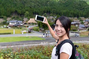 Travel Woman taking photot on cellphone in miyama of Kyoto