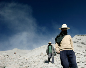 Residents walk at a side of the volcano Ubinas in the town of Ubinas