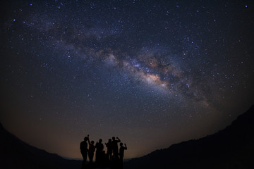 Landscape with milky way, Night sky with stars and silhouette of happy people standing on moutain, Long exposure photograph, with grain.