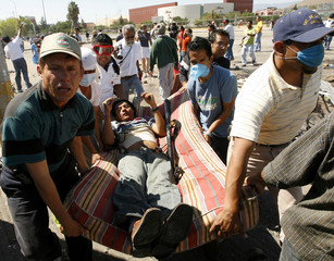People carry injured protester after clashes with Federal police officers in Oaxaca City, Mexico