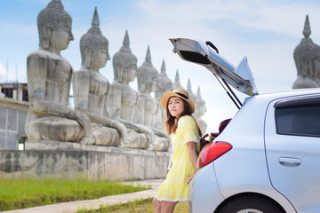 Asian woman travel by car in Thailand with Buddha park is background.
