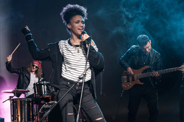 Female singer with microphone and rock and roll band performing hard rock music on stage