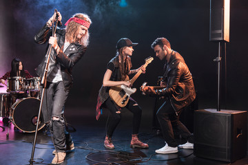 Young multiethnic rock and roll band performing music on stage