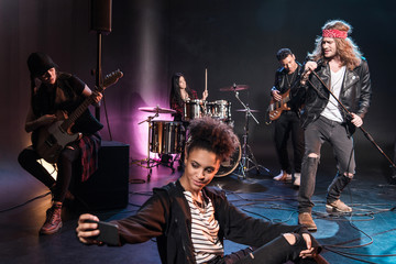 Young woman taking selfie with rock and roll band performing concert on stage