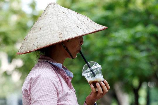 A fruit vendor drinks iced coffee in Hanoi