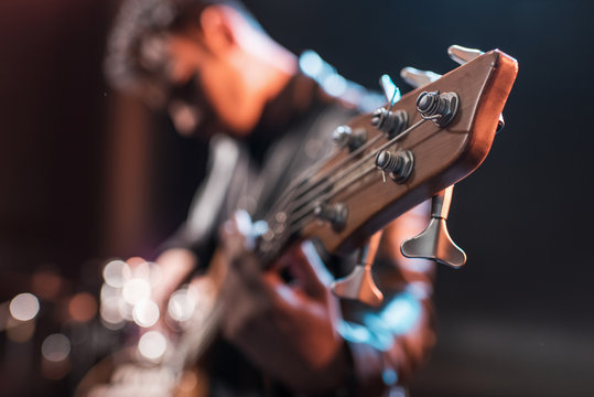 Electric guitar player playing hard rock music with bass guitar on stage