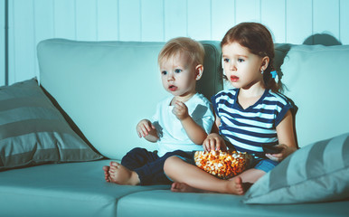 Children brother and sister watching TV in evening
