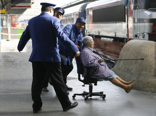 French railways agents evacuate an injured passenger after a commuter train failed to brake as it entered the Paris Est station